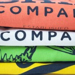 Four printed t-shirts stacked on top on each other in contrasting colours showing discharge print close up