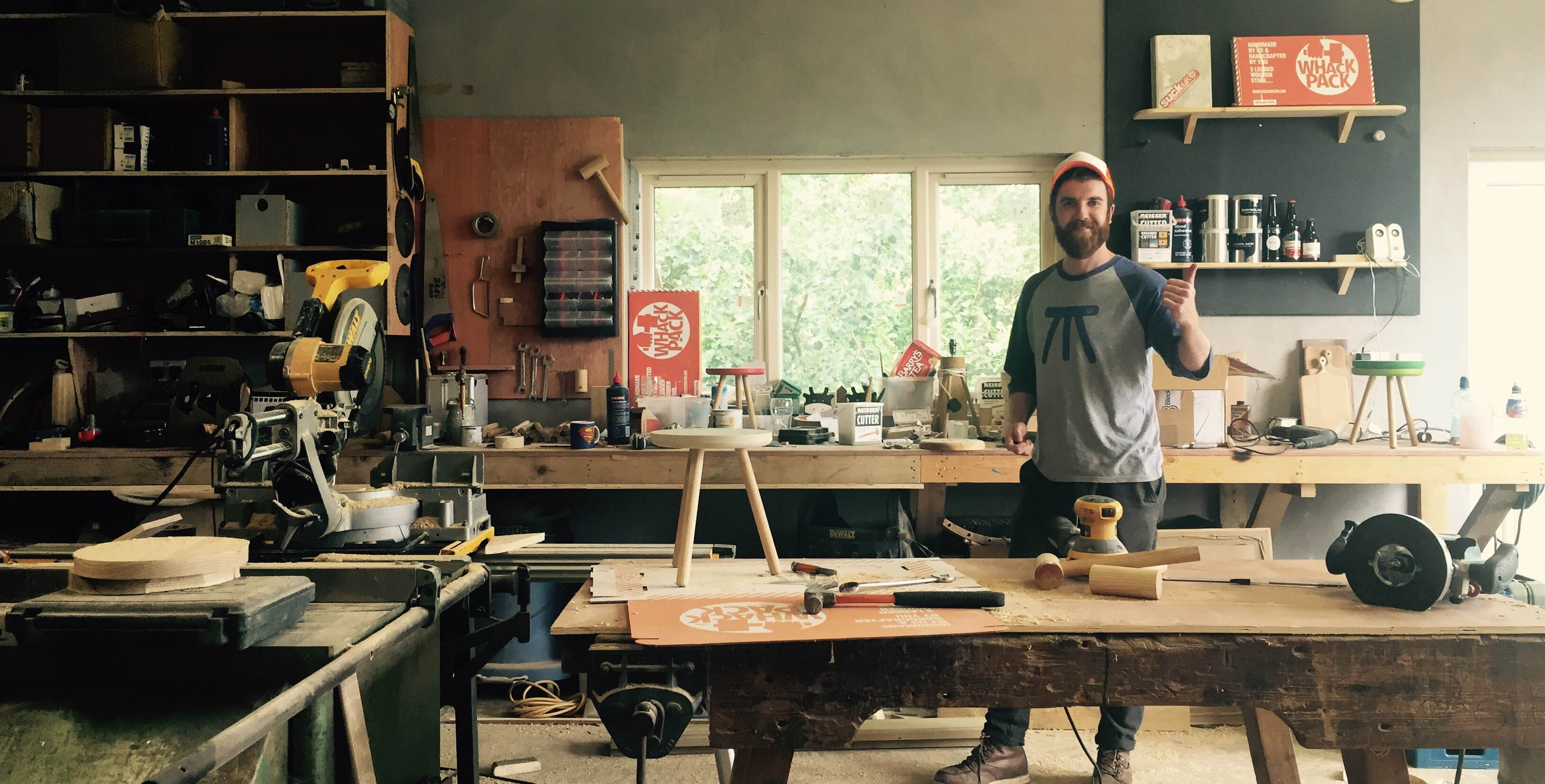 Man in workshop wearing a printed t-shirt with an abstract stool image on front.