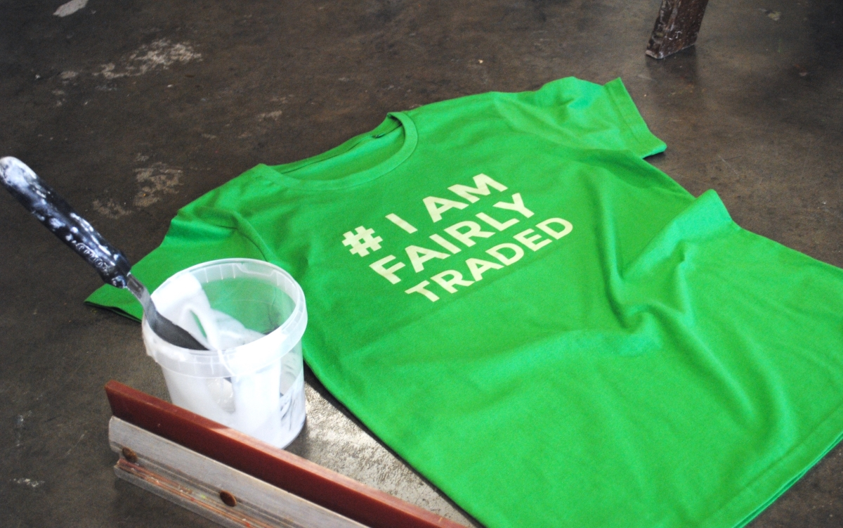 A green organic and fairtrade t-shirt on the ground with water-based ink with print on front , I am fairly traded