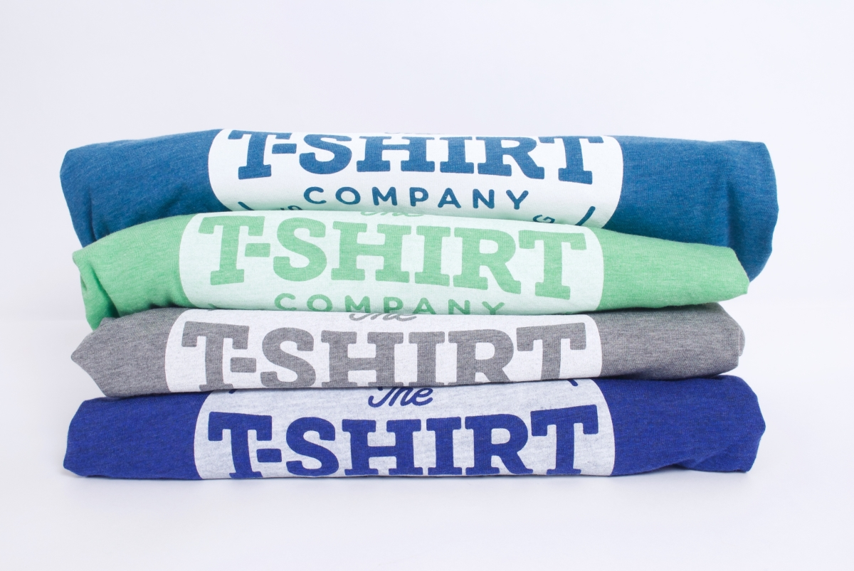 4 triblend tees in green, grey,  aqua and true royal blue stacked on top of each other with the t-shirt company logo printed in white discharge waterbased ink visible on each Bella and Canvas t-shirt