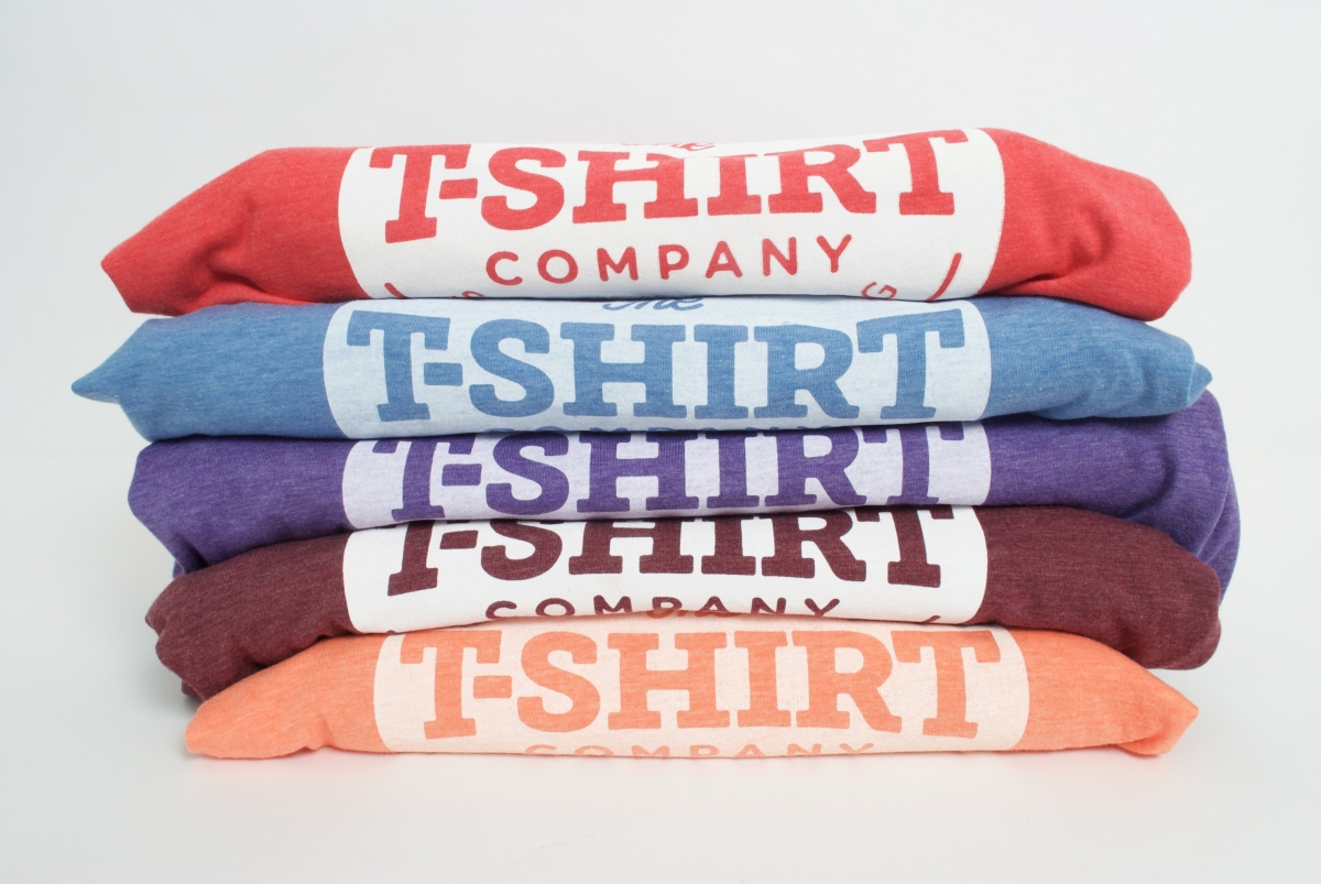 Five Bella and Canvas triblend tees in orange, red, blue,  purple and maroon stacked on top of each other with the t-shirt company logo clearly visible showing the different effects of white discharge ink on each colour way.